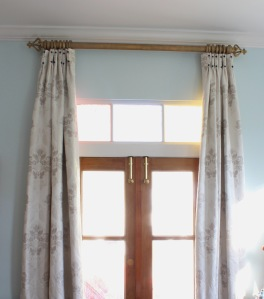 cream drapes with inverted pleats and navy covered buttons